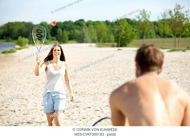 Couple playing badminton on the beach