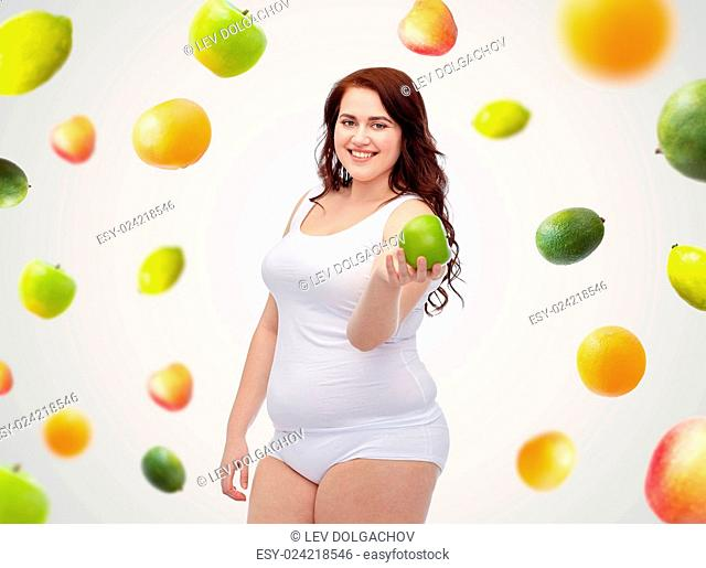 weight loss, diet, slimming, healthy eating and people concept - happy young plus size woman in underwear with green apple over fruit background