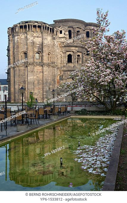 Porta Nigra, World Heritage Site, with fountain and blooming magnolia, Trier, Germany