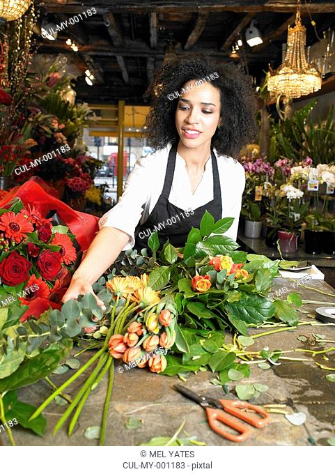 Young female florist preparing bouquet in shop, smiling