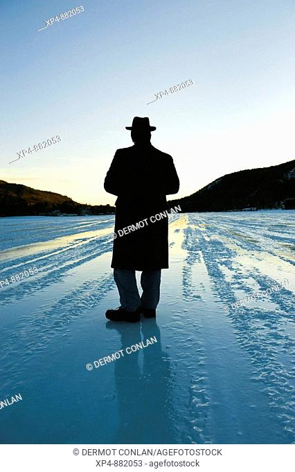 Silhouette of a man wearing an overcoat and a hat standing on a frozen lake strating off to the horizon, his back is to the camera