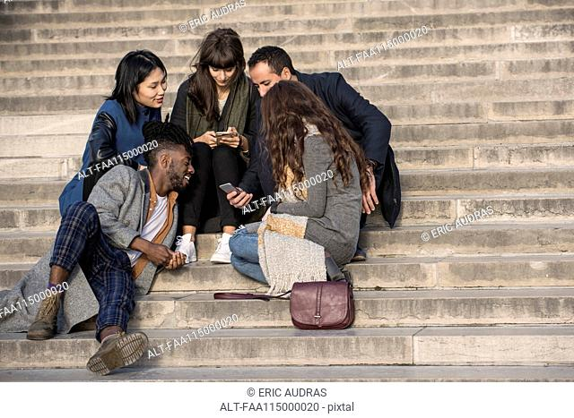 Friends sitting on steps and using smart phone