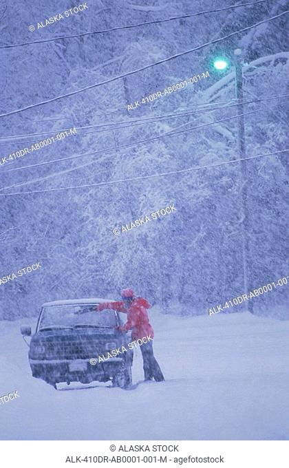 Anchorage Southcentral Alaska Man Wiping Snow Car Winter Light Snowing Trees
