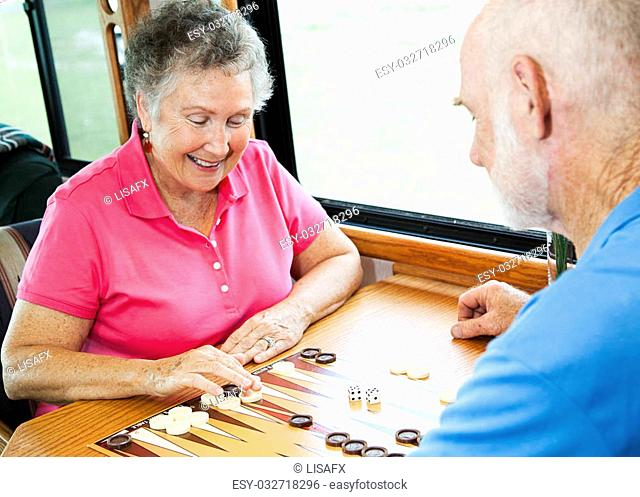 Senior couple in the kitchen of their motor home playing backgammon