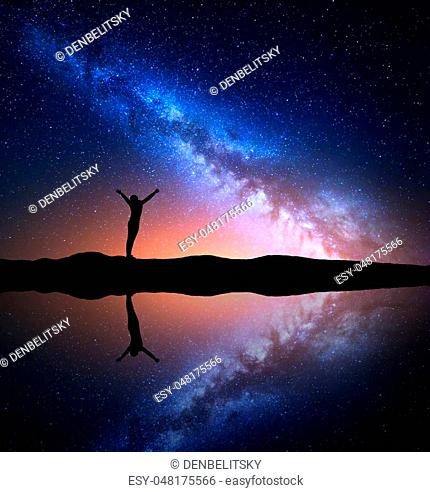Milky Way. Night starry sky and silhouette of a standing woman with raised up arms on the hill near the lake with reflection in water