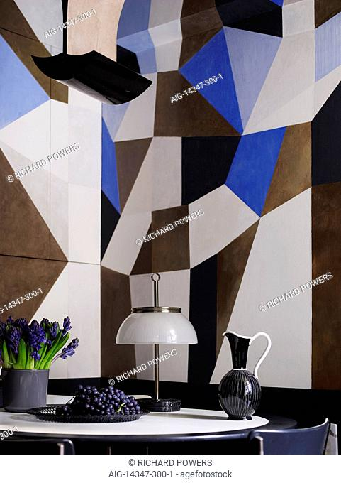 Small round table with jug, lamp, grapes and flowers in front of abstract artwork on walls in residential house, France