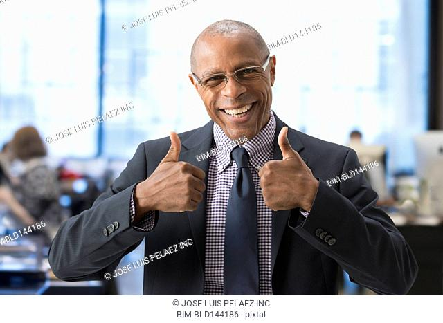 Black businessman giving thumbs up in office