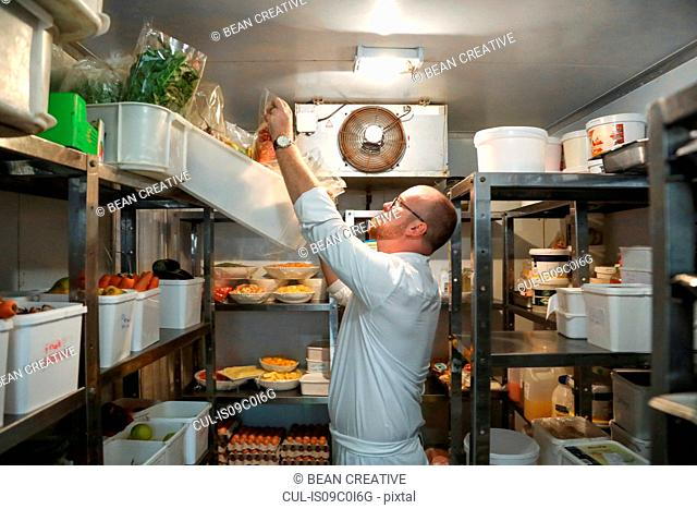 Chef checking stock of goods in storage room