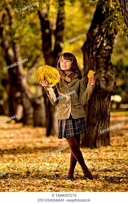 vertical photo, beautiful little girl with autumnal leaf, in park