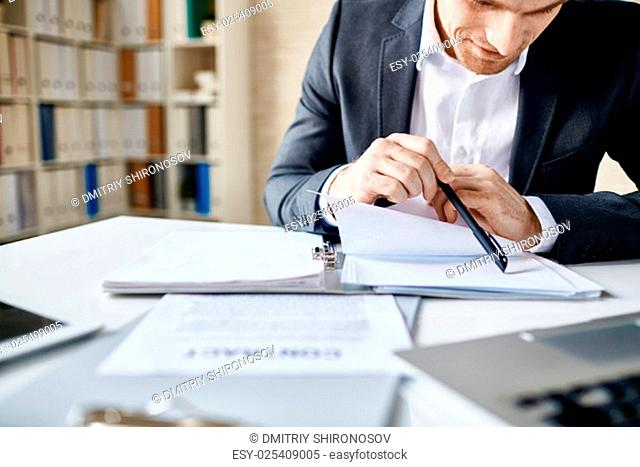 Businessman reading documents or notes in office