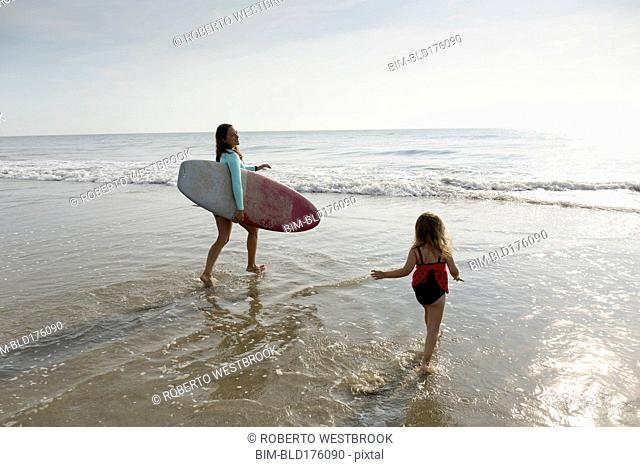 Mother and daughter playing in waves on beach