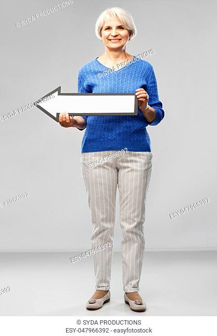 smiling senior woman with big leftwards arrow