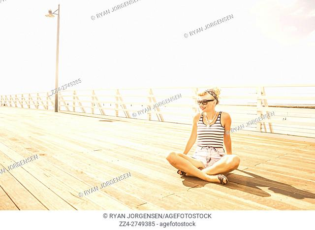 Dreamy high-key portrait of a relaxing woman sitting crossed legged on a wooden jetty. Marine Serenity