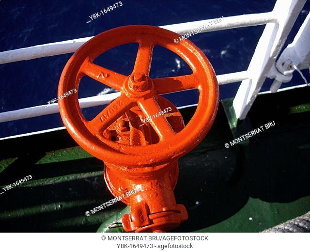 Orange iron wheel on dark green ferryboat deck