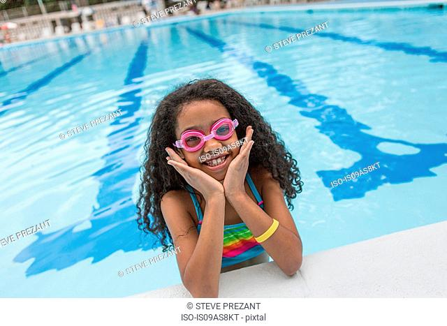 Portrait of girl in swimming pool wearing swimming goggles, looking at camera smiling