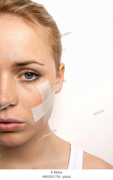 Young woman with plaster in her face