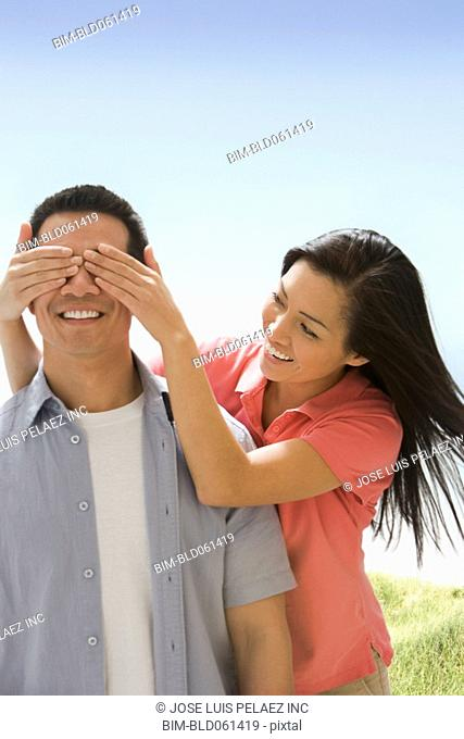 Asian woman covering boyfriend's eyes