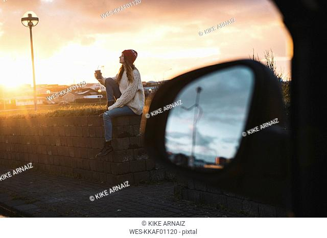 Iceland, young woman with coffee to go at sunset, wing mirror