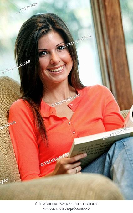 Girl sitting on couch reading a book