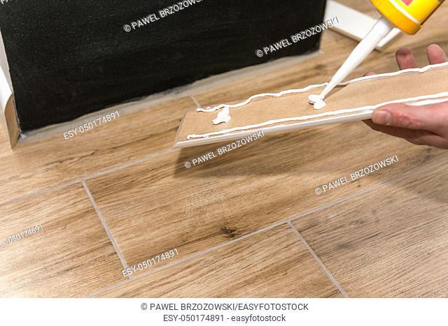 Mans hands using caulking gun to install white skirting board. Do it yourself
