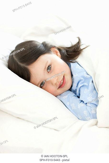 MODEL RELEASED. Young girl lying in bed