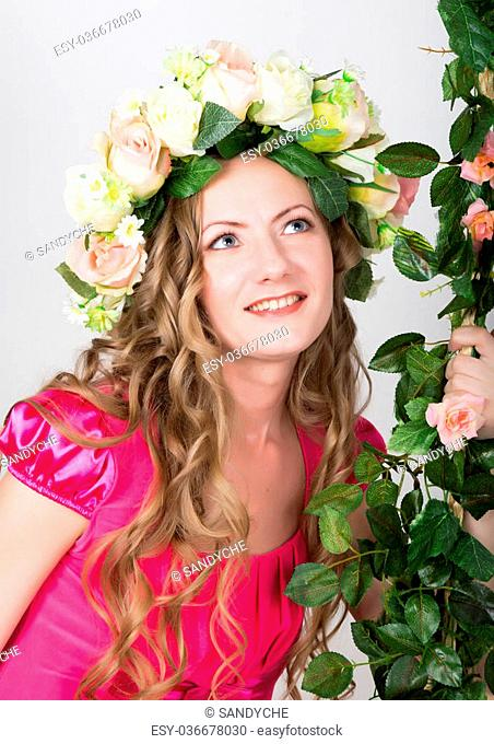 Beautiful young leggy blonde in a little red dress on head a wreath of flowers, rope wrapped vine and ivy