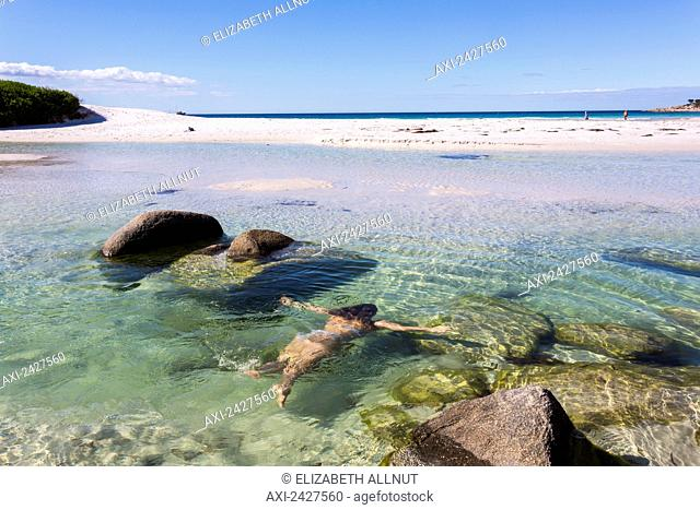 A young woman swimming off Bay of Fires beach; Tasmania, Australia