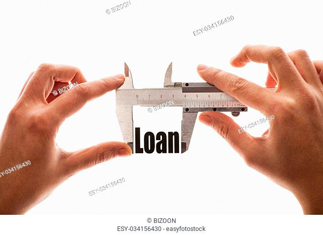 "Close up shot of a caliper, measuring the word """"Loan"""""