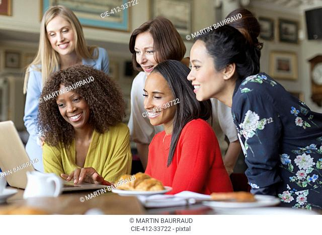 Women friends using laptop at restaurant table