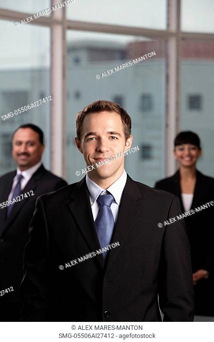 Caucasian man standing in front of his colleagues