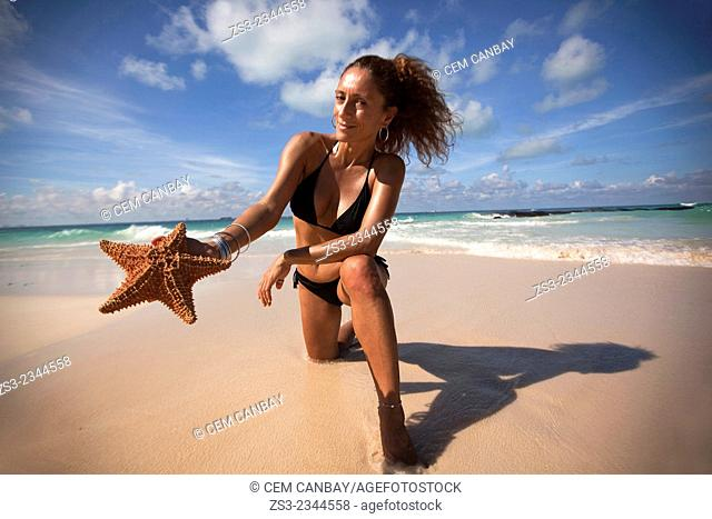 Woman holding a starfish on the beach, Isla Mujeres, Cancun, Quintana Roo, Yucatan Province, Mexico, Central America