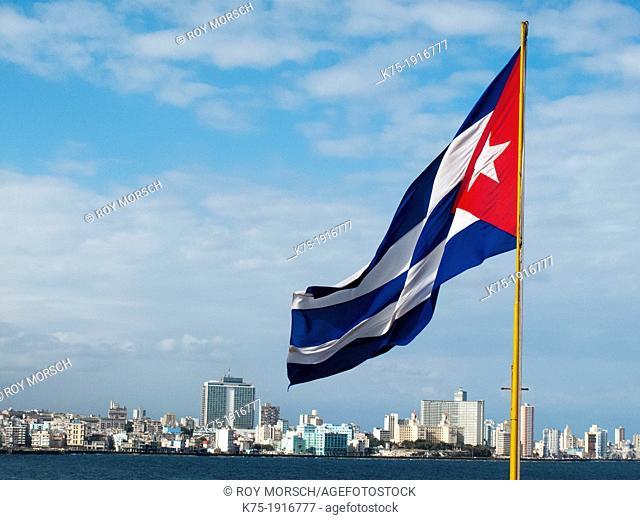 Cuban flag flies with Havana skyline in background