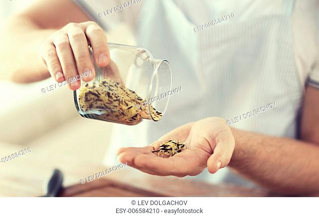 cooking and home concept - close up of male emptying jar with mixture of white and wild black rice
