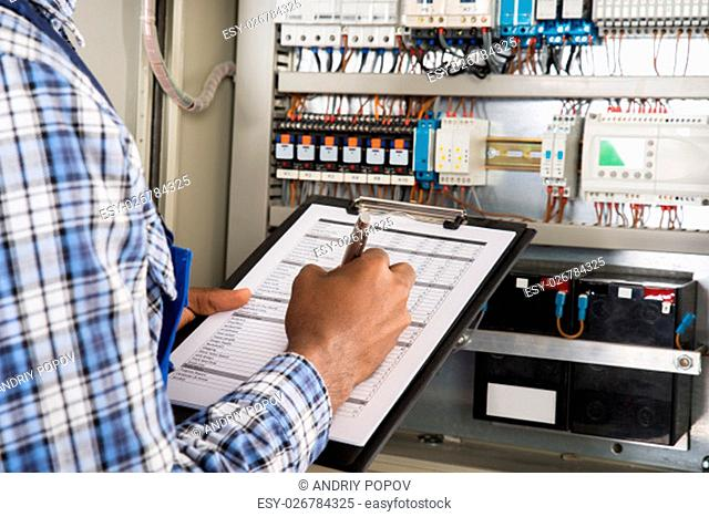 Close-up Of Male Technician Writing On Clipboard In Front Of Fusebox