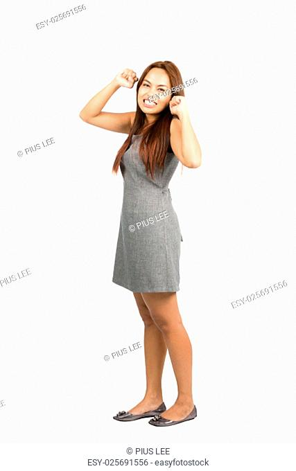 Teeth clenched Asian woman in gray dress with light brown hair, balled fists, looking at camera throwing immature temper tantrum, fed up, annoyed, irritated