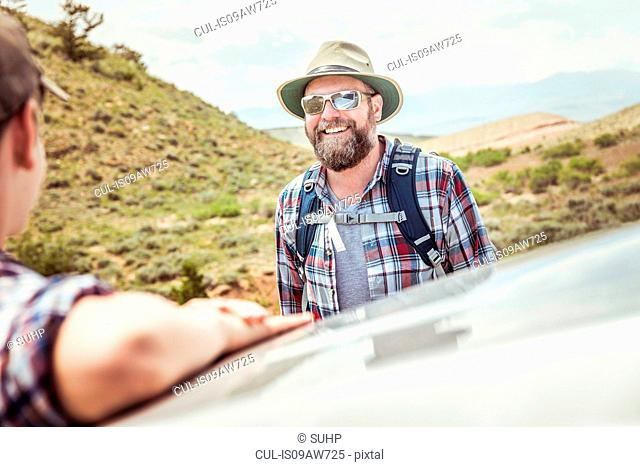 Man and teenage son on hiking road trip leaning on car roof in landscape, Bridger, Montana, USA