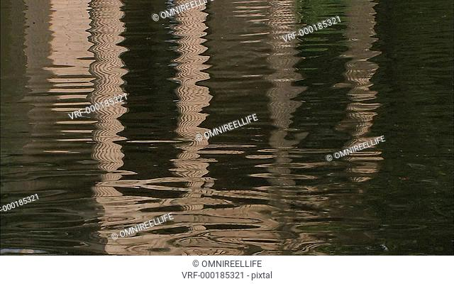 Four Roman columns reflected in water