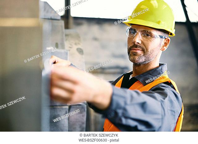 Portrait of confident man wearing protective workwear working in factory