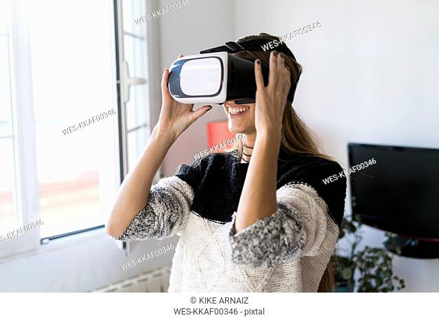Young woman wearing VR glasses at home