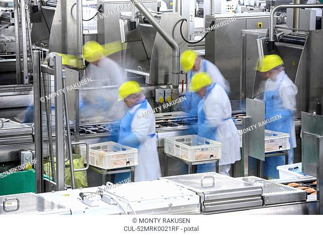 Blurred view of workers in factory