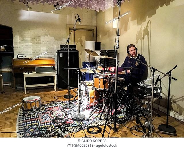 Berlin, Germany. Music student Lucas drumming away, recording beats and sounds inside a professional music recording studio
