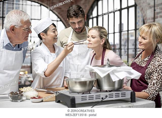 Woman smelling ingredient in cooking class