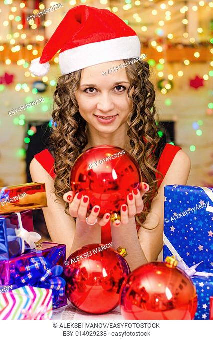 Young beautiful girl sitting at a table with Christmas gifts in the Christmas atmosphere