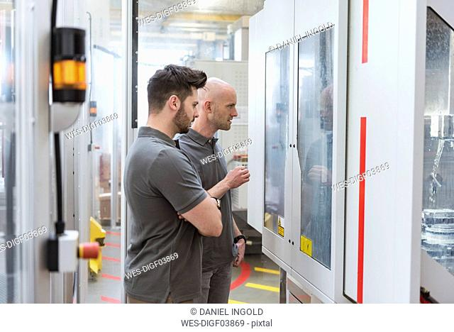 Two men examining machine in modern factory