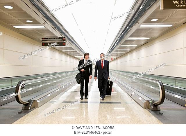 Caucasian businessmen walking in airport
