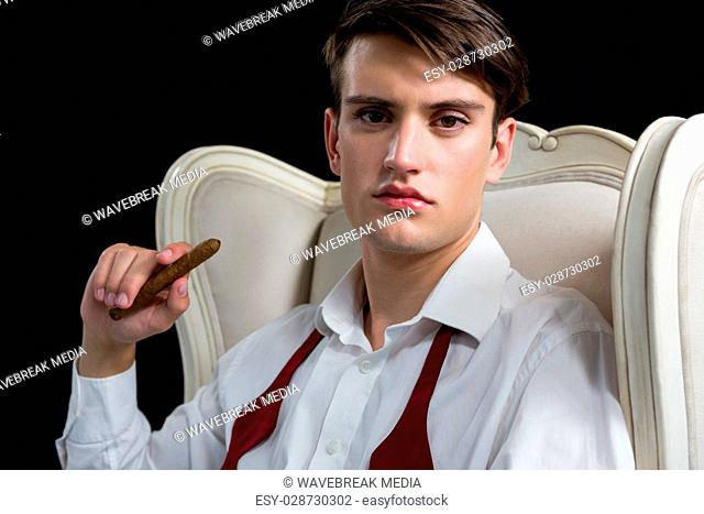 Androgynous man sitting on chair with cigar against black background