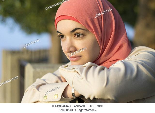 Beautiful Muslim woman leaning on the fence looking away outdoors