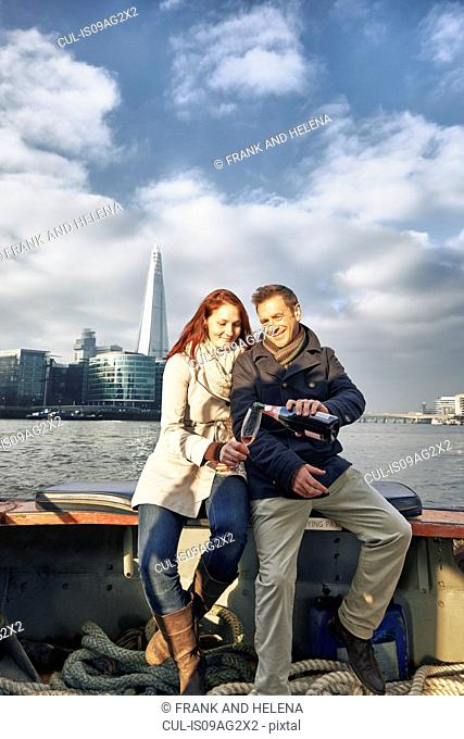 Romantic couple on Thames boat sharing pink champagne, London, UK