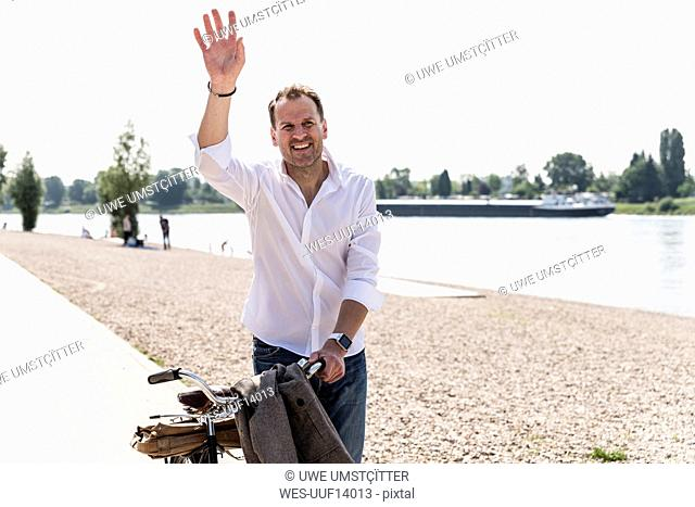 Mature man with bike waving at Rhine riverbank