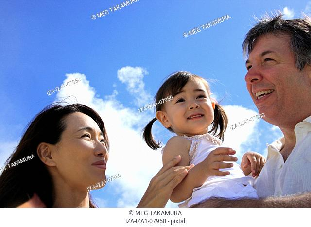 Low angle view of a mature man with a mid adult woman carrying his daughter and smiling